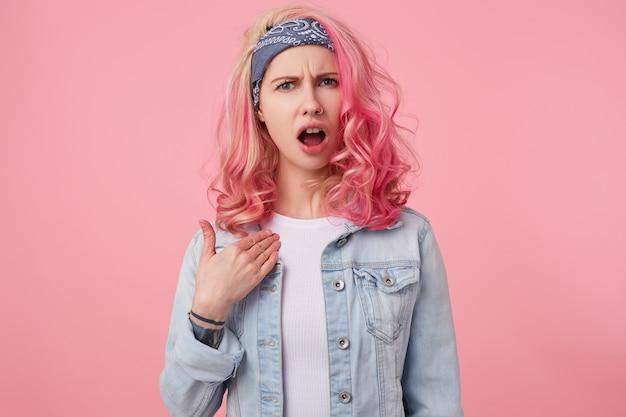 Une jolie femme perturbée aux cheveux roses, la bouche ouverte se demande pourquoi elle a été accusée de ce qu'elle n'a pas fait, se montre du doigt et a l'air mécontente, se lève.