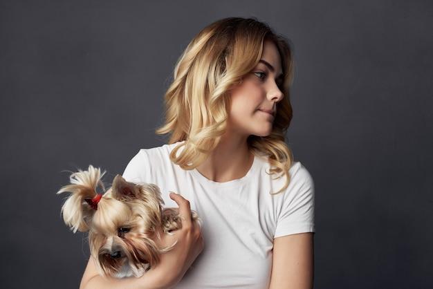 Jolie femme avec un petit chien maquillage posant fond isolé