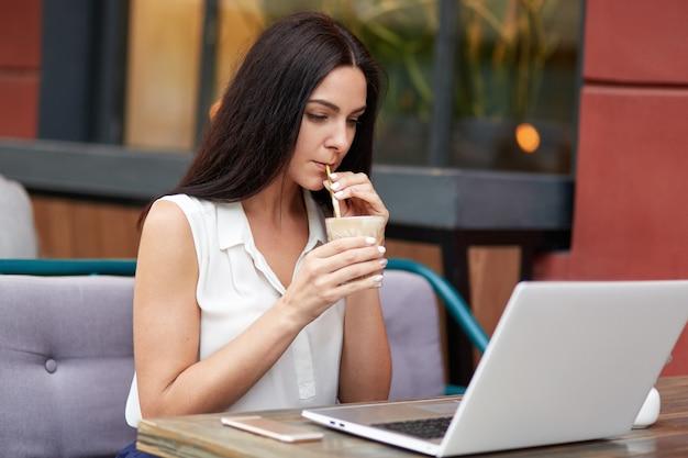 Jolie femme pigiste concentrée sur un ordinateur portable, lit les informations nécessaires lors de la préparation de l'examen, boit un cocktail, entouré d'appareils modernes, est assis contre l'intérieur du restaurant