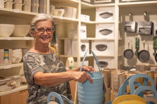 Jolie femme plus âgée faisant du shopping dans un magasin de rénovation domiciliaire, regardant la caméra en souriant