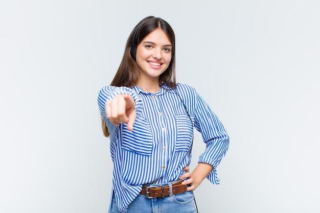 Jolie femme pointant la caméra avec un sourire satisfait, confiant et amical, vous choisissant