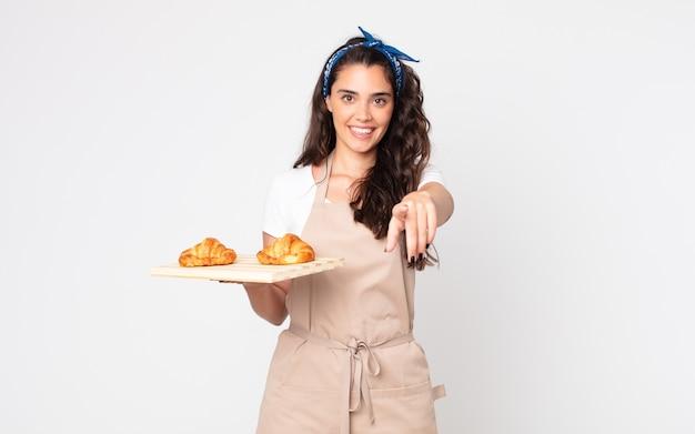Jolie femme pointant sur la caméra vous choisissant et tenant un plateau de croissants