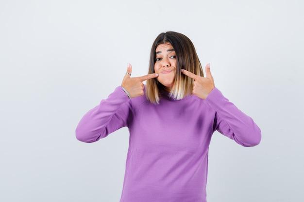 Jolie femme pointant sur ses joues gonflées en pull violet et à la vue ludique, de face.