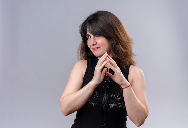 Jolie femme portant un chemisier noir à la pensée sournoisement joignant les mains