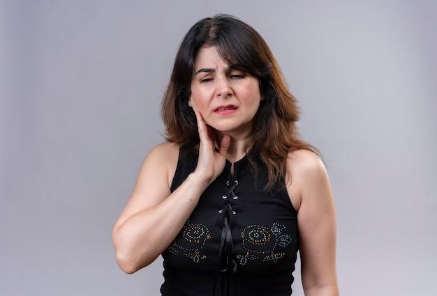 Jolie femme portant un chemisier noir souffrant de maux de dents
