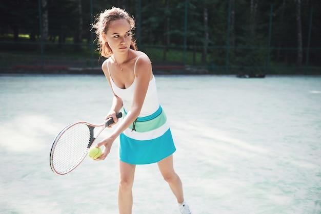 Une jolie femme portant un court de tennis sportswear sur le court.