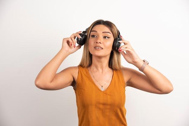 Jolie femme portant des écouteurs sur fond blanc.