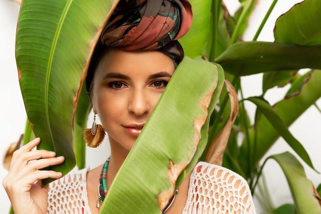 Jolie femme portant un foulard coloré comme un turban et de grandes boucles d'oreilles rondes