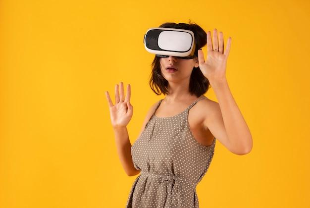 Jolie femme portant des lunettes de réalité virtuelle sur l'espace jaune