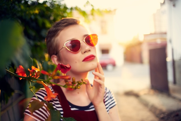 Jolie femme portant des lunettes de soleil à l'extérieur de la mode posant des fleurs. photo de haute qualité