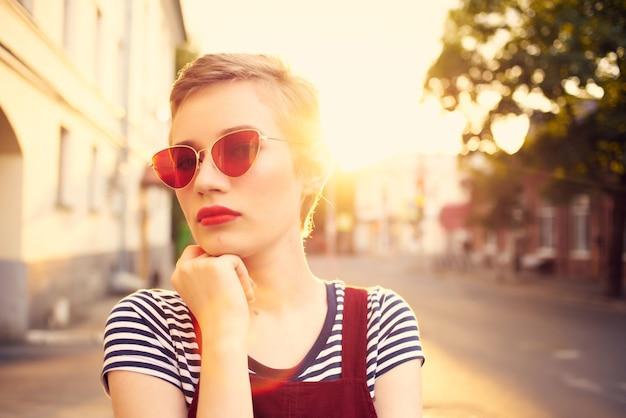 Jolie femme portant des lunettes de soleil à l'extérieur posant l'été