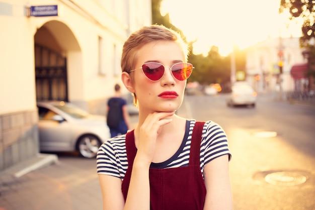 Jolie femme portant des lunettes de soleil posant à l'extérieur en gros plan