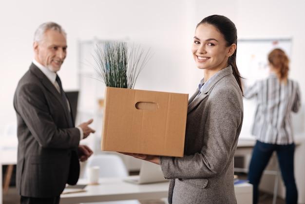Jolie femme portant un nouveau costume souriant tout en regardant à l'avant, en gardant la boîte avec la papeterie dans les deux mains