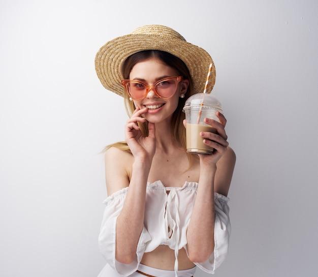 Jolie femme portant des vêtements de mode portant des chapeaux et des cocktails de luxe amusant