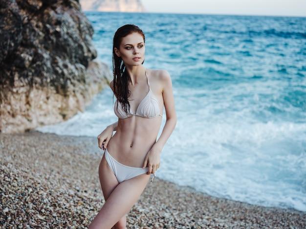 Jolie femme posant maillot de bain blanc paysage océan été