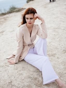 Jolie femme posant près des rochers dans le voyage modèle de sable