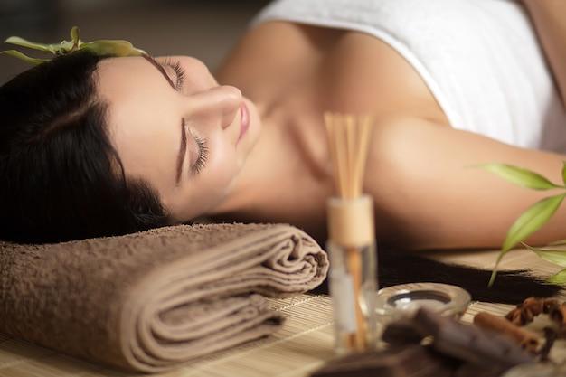 Jolie femme pose dans un salon spa avec des yeux fermés et détendue