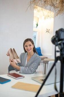 Jolie femme positive ayant un cadeau sur son blog tout en voulant attirer de nouveaux téléspectateurs