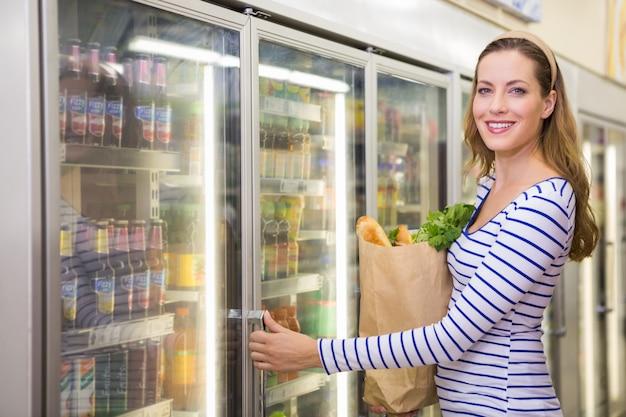 Jolie femme prenant un produit sur le frigo