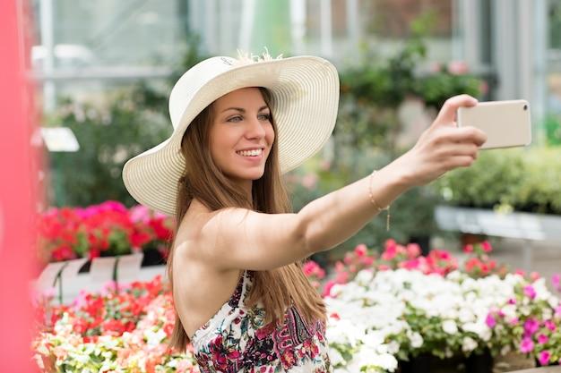 Jolie femme prenant un selfie dans une pépinière