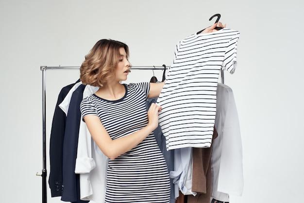 Jolie femme près de vêtements accro du shopping fond isolé