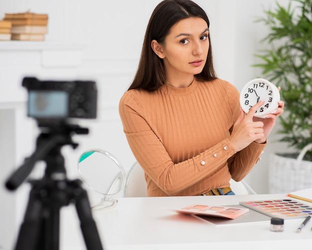 Jolie femme présentant une horloge