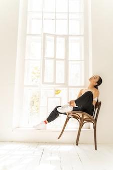 Jolie femme profitant d'une journée ensoleillée près de la fenêtre
