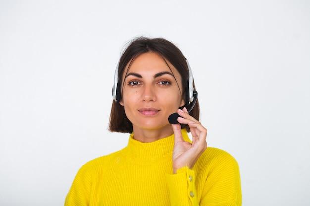 Jolie femme en pull jaune sur un gestionnaire blanc avec un casque heureux sourire accueillant positif