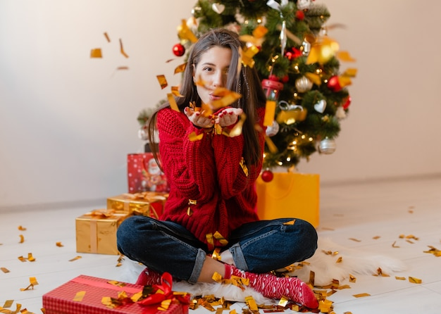 Jolie femme en pull rouge assis à la maison à l'arbre de noël jetant des confettis dorés entouré de cadeaux et coffrets cadeaux