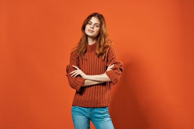 Jolie femme en pull rouge posant fond isolé studio