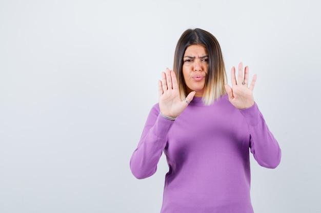 Jolie femme en pull violet montrant un geste d'arrêt et ayant l'air effrayé, vue de face.