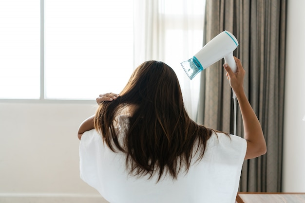 Jolie femme en pyjama assis sur son lit et séchant ses cheveux le matin