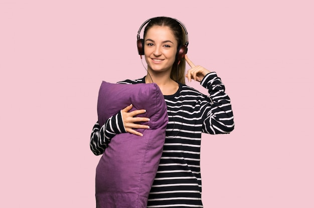 Jolie femme en pyjama, écouter de la musique avec des écouteurs sur mur rose isolé