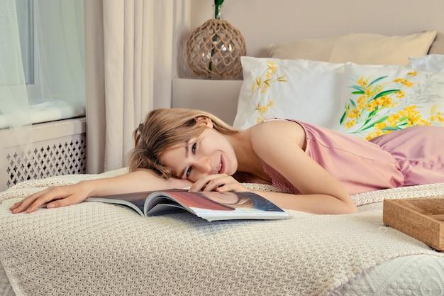 Jolie femme en pyjama de soie au lit, feuilletant un magazine