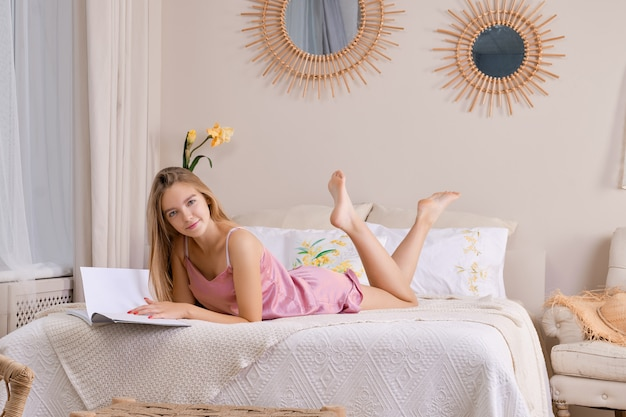 Jolie femme en pyjama de soie au lit feuilletant un magazine