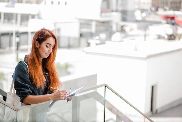 Jolie femme qui écrit sur les escaliers