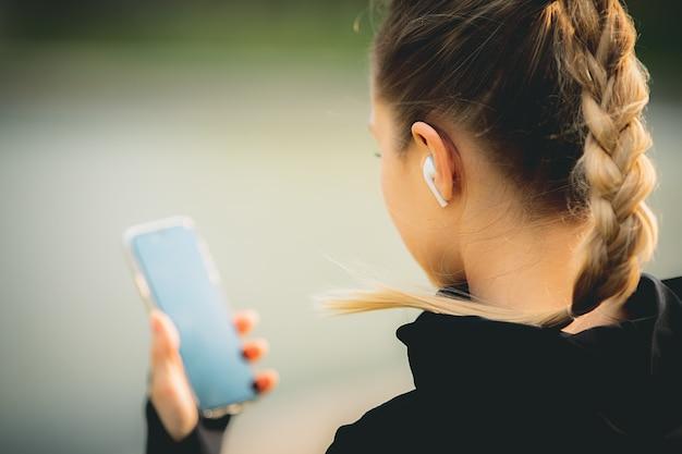 Jolie femme de race blanche à l'aide de son téléphone, casque sans fil lors de l'exécution dans le parc