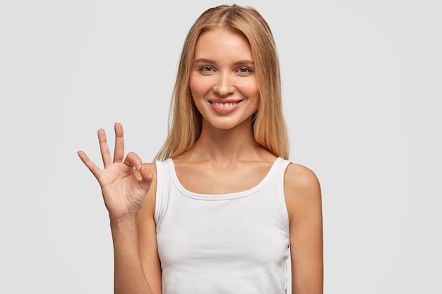 Jolie femme de race blanche aux cheveux longs, expression satisfaite, montre un signe correct, se sent heureuse après avoir rencontré un beau mec, isolé sur un mur blanc. expressions faciales humaines, langage corporel