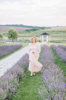 Jolie femme de race blanche blonde mature avec une robe beige clair qui traverse joyeusement un champ de lavande souriant à la caméra