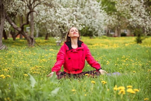 Jolie femme de race blanche médite à l'extérieur dans le jardin fleuri