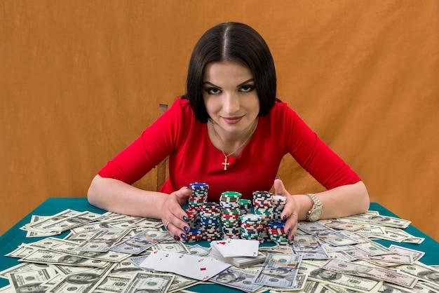 Jolie femme rassemblant des piles de jetons de casino