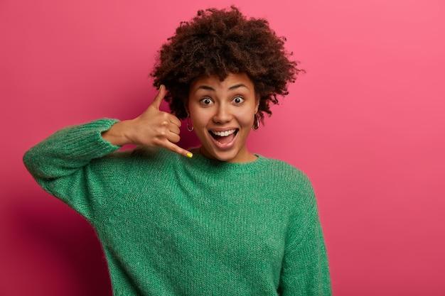 Jolie femme ravie fait signe de téléphone, dit de me rappeler, sourit joyeusement, communique avec des gestes, vêtue d'un pull vert, pose sur un mur rose. n'oublie pas d'appeler, d'être en contact