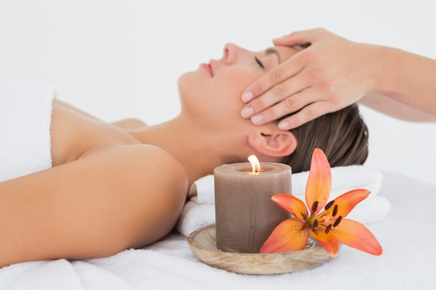 Jolie femme recevant un massage de la tête au centre de spa