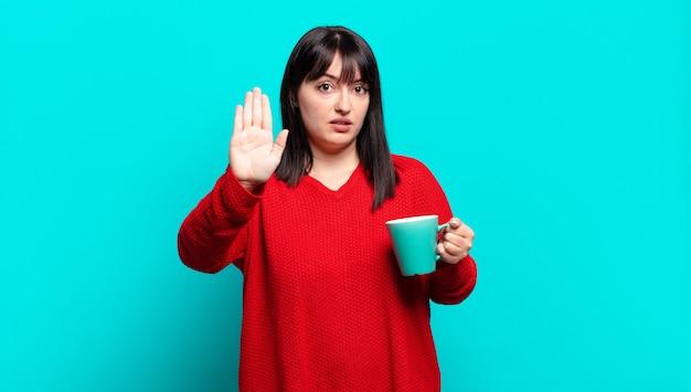 Jolie femme à la recherche sérieuse, sévère, mécontente et en colère montrant la paume ouverte faisant le geste d'arrêt