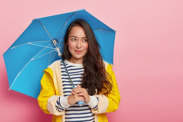 Jolie femme réfléchie aux cheveux raides foncés, tient un parapluie bleu, marche pendant une journée fraîche, se protège de la pluie