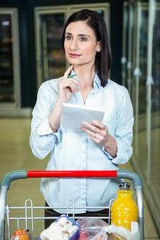 Jolie femme regardant un produit sur une étagère et tenant une liste d'épicerie