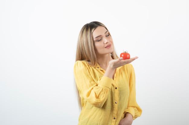 Jolie femme regardant la tomate rouge sur le mur blanc.
