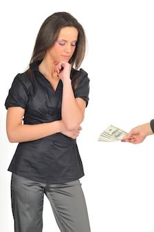 Jolie femme regarde les billets d'un dollar dans la main. fille qui pose en chemisier gris et pantalon avec la main près du visage