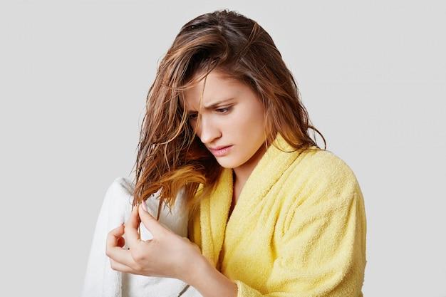 Jolie femme regarde désespérément les pointes fourchues des cheveux après avoir pris une douche