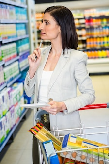 Jolie femme, regarder produit, sur, étagère, et, tenue, liste épicerie